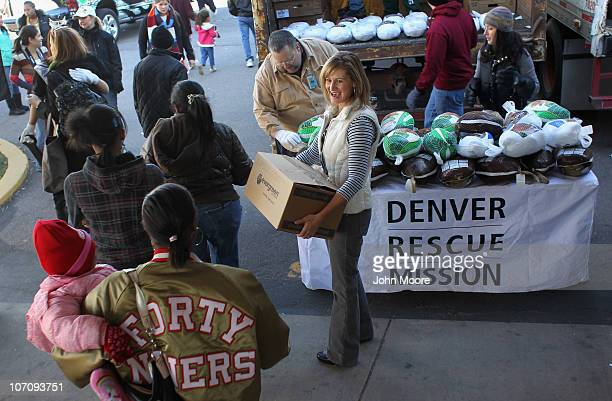 Volunteers pass out food aid at the 'banquet in a box' distribution held by the Denver Rescue Mission on November 23 2010 in Denver Colorado The...