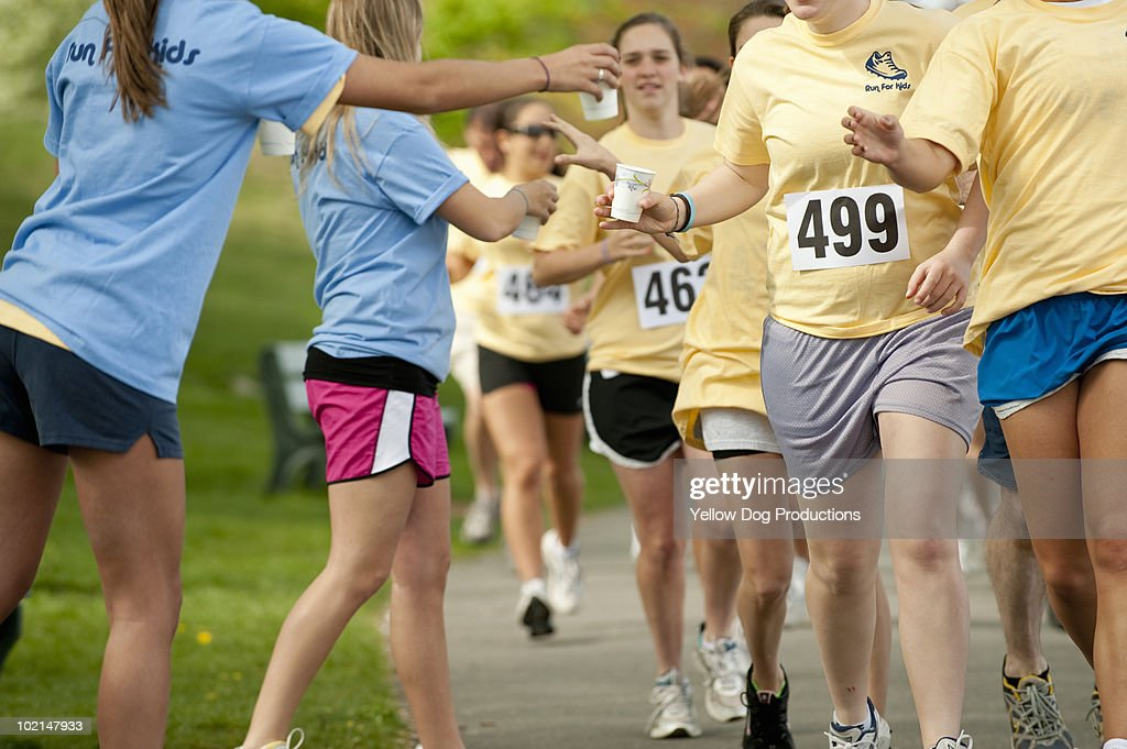 Volunteers passing out water during running race