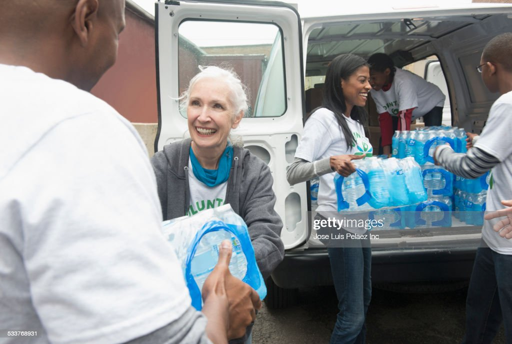 Volunteers passing stacks of bottled water from delivery van