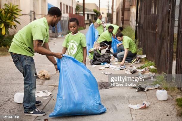 Volunteers picking up litter in alley