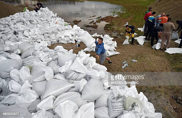 Volunteers place sand bags at an entrance of the former chemical plant 'Zorka' in the city of Sabac 100 kilometers west of Belgrade on May 18 2014...