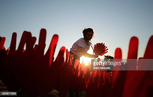Volunteers plant hands to help create the Sea Of Hands Installation artwork at Barangaroo Reserve on May 27 2016 in Sydney Australia The installation...