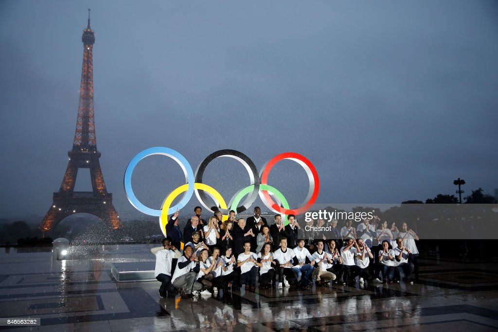 Volunteers pose after the unveiling of the Olympic rings on the esplanade of Trocadero in front of the Eiffel tower after the official announcement of the attribution of the Olympic Games 2024 to the city of Paris on September 13, 2017 in Paris, France. For the first time in history, the International Olympic Committee (IOC) confirms two summer Games host cities at the same time, Paris will host the Olympic Games in 2024 and Los Angeles in 2028.