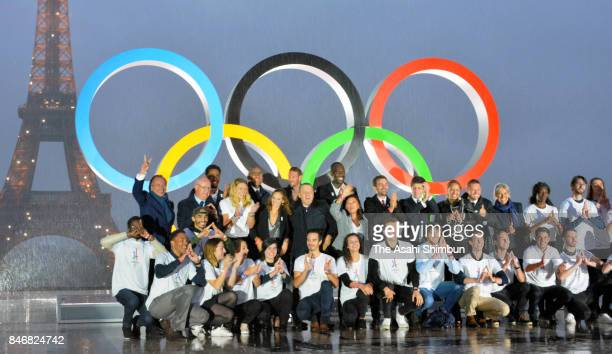 Volunteers pose after the unveiling of the Olympic rings on the esplanade of Trocadero in front of the Eiffel tower after the official announcement...