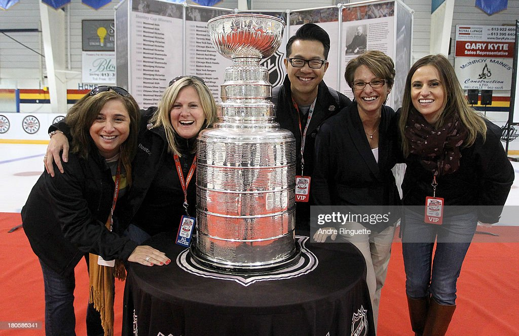 Volunteers pose for a picture with the Stanley Cup at the Stirling and District Recreation Centre during Kraft Hockeyville Day 2 on September 14, 2013 in Stirling, Ontario, Canada.