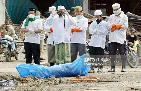 Volunteers pray in front of a dead body in Banda Aceh 12 January 2005 Indonesia on Wednesday stood firm on tough restrictions for foreign aid workers...