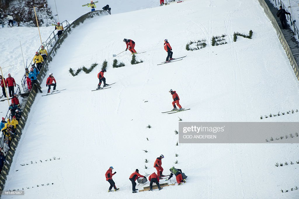 Volunteers prepare a show jump after the cancellation of the FIS Ski Jumping World Cup individual large hill competition on the Muehlenkopfschanze hill in Willingen, western Germany on February 10, 2013. AFP PHOTO / ODD ANDERSEN