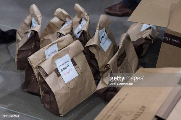 Volunteers prepare lunch bags reading 'Child' for migrants arriving from Athens at the SaintExupery international airport in ColombierSaugnieu near...
