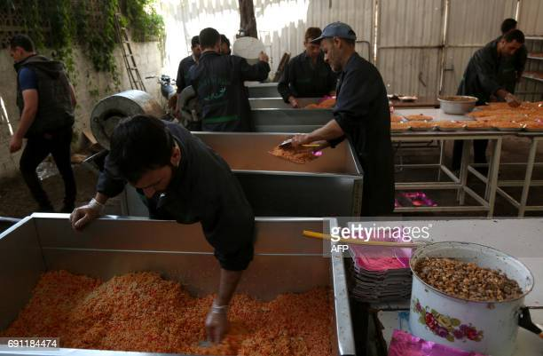 Volunteers prepare Ramadan meals that will be distributed to impoverished families and Muslim devotees breaking their fast at a charity kitchen in...