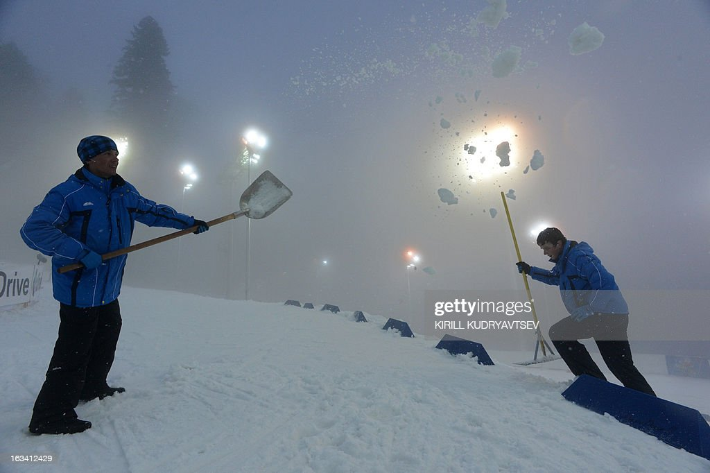 Volunteers prepare the raceway in fog during a training session before Women 7.5 km Sprint during IBU World Cup Biathlon at Laura Cross Country and Biathlon Center in the Russian Black Sea resort of Sochi on March 9, 2013.