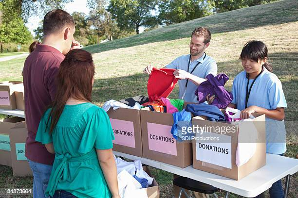Volunteers receiving clothes donations from donors at a donation center