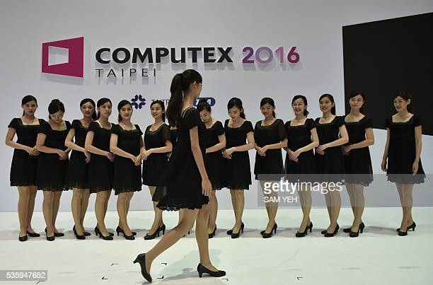 Volunteers rehearse in front of the Computex logo during the annual Computex computer exhibition in Taipei on May 31 2016 More then 5000 booths from...