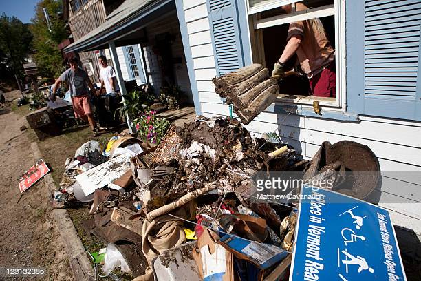 Volunteers remove mud and debris from a real estate office that was flooded in tropical storm Irene on West Main Street on August 31 2011 in...