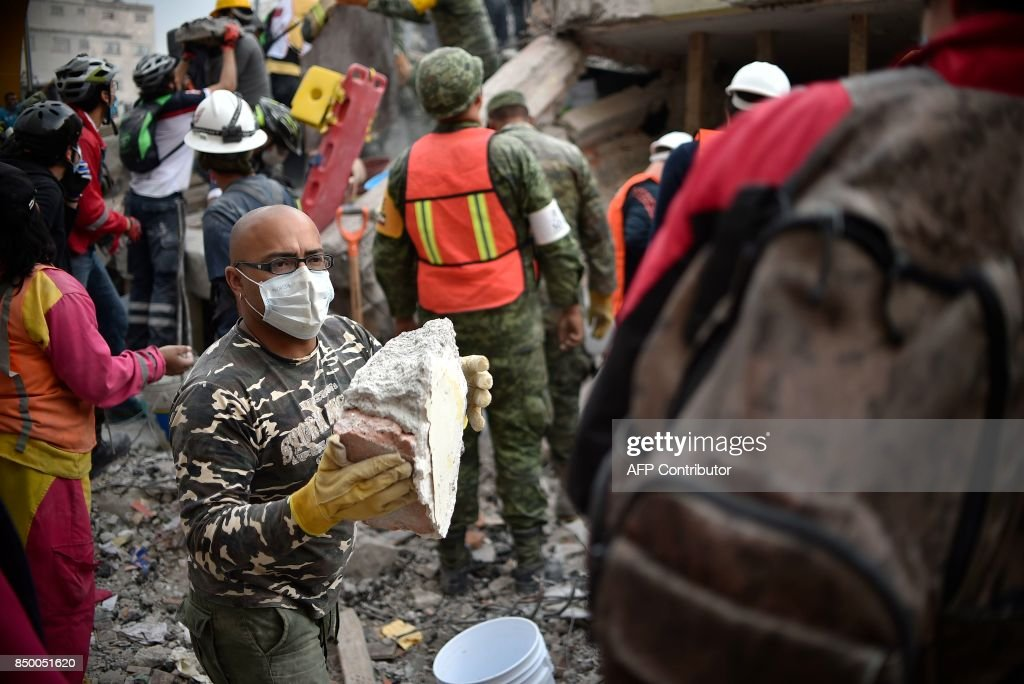 Volunteers remove rubble during the search for survivors in a flattened building in Mexico City on September 20, 2017 after a strong quake hit central Mexico on the eve killing at least 240 people. A powerful 7.1 earthquake shook Mexico City on Tuesday, causing panic among the megalopolis' 20 million inhabitants on the 32nd anniversary of a devastating 1985 quake. / AFP PHOTO / Yuri CORTEZ