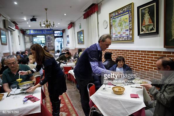 Volunteers serve free dinner to homeless people at Robin Hood restaurant on December 5 2016 in Madrid Spain Association Messengers Of Peace...