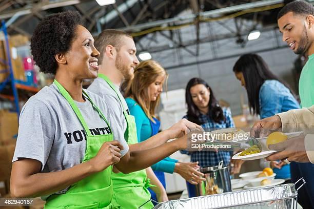 Volontaires qui sert des repas chaud de Soupe populaire