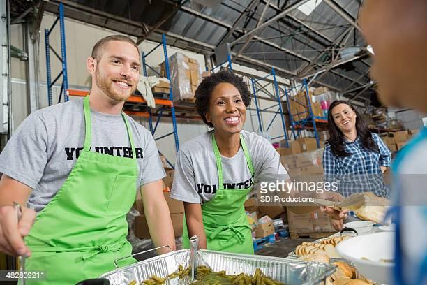 Freiwillige mit warmen Speisen für Menschen in Gemeinschaft Volksküche