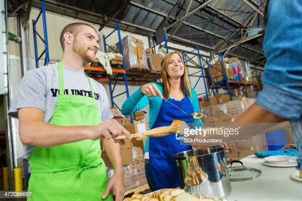 Volontaires qui sert repas pour les personnes à la banque alimentaire Soupe populaire