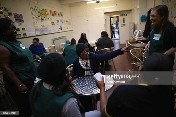 Volunteers share a joke with visitor Louisa Millen at a Food Bank depot at St Paul's Church in Brixton on October 23 2012 in London England The need...