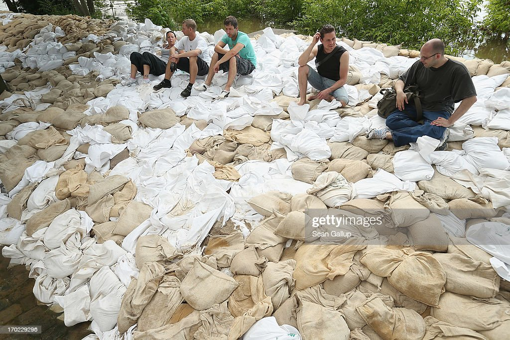 Volunteers sit on sandbags after stacking them against rising floodwaters in the Werder district of the city center next to the swollen Elbe river on June 9, 2013 in Magdeburg, Germany. Magdeburg is enduring its highest floodwaters in its 1,200 year history and local authorities have called on 23,000 residents from outlying areas to evacuate their homes. Catastrophic flooding has hit portions of southern and eastern Germany that has left at least seven people dead and forced tens of thousands to flee their homes. Towns in northern Germany downstream from the Elbe are also bracing for floods in coming days.