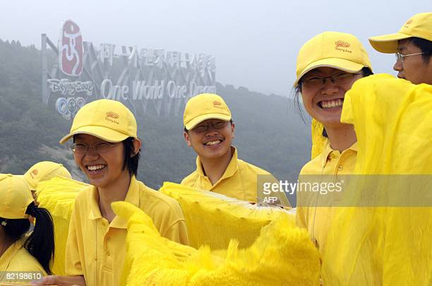 Volunteers smile before the Olympic torch relay procedes along a section of the Great Wall in Badaling outside Beijing on August 07 2008 a day before...