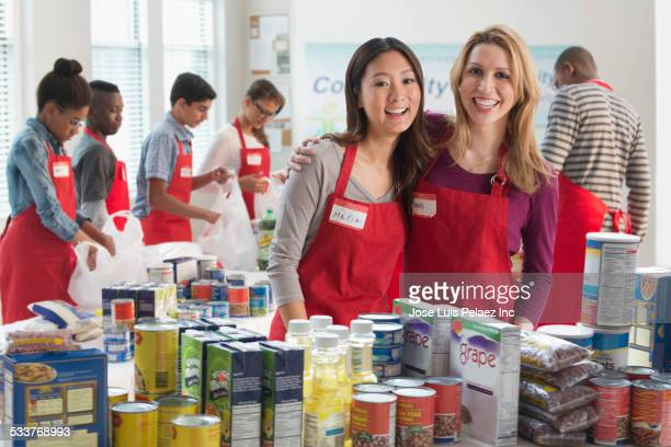 Volunteers smiling near canned goods at food drive