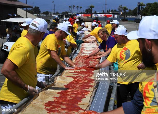 Volunteers spread tomato sauce and cheese onto the pizza base as they successfully break the Guinness World Records title for Longest pizza with a...