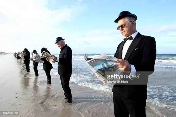 Volunteers stand and read the morning newspaper while 'waiting for the bus' at Henley Beach on January 8 2012 in Adelaide Australia Surrealist artist...