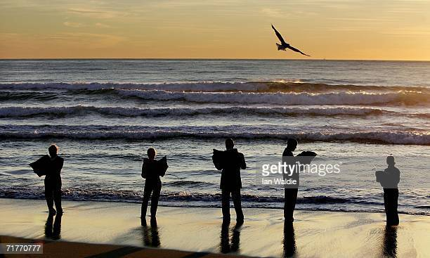 Volunteers stand at the waters edge and read newspapers to form a 'human sculpture' on Manly Beach September 2 2006 in Sydney Australia Artist Andrew...