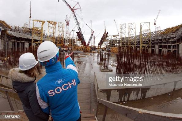 Volunteers stand on the ground of the construction site of the Olympic stadium 'Fisht' on February 10 2012 in Sochi Russia The 'Fisht' will host the...