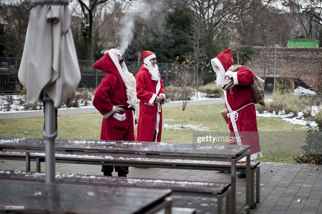 Volunteers stand together dressed as Santa during their annual, pre-Christmas gathering at the cafeteria of the Studentenwerk Nord student support service on December 1, 2012 in Berlin, Germany. The students, mostly from Berlin Technical University (Technische Universitaet Berlin), have completed a Santa workshop and will visit company parties in December and families on Christmas Eve as a way to make a little money to help fund their studies.