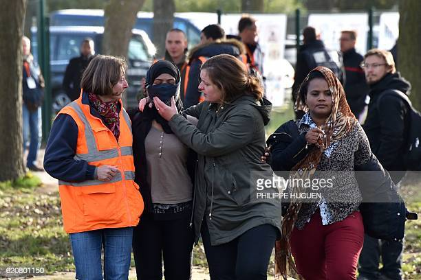 Volunteers support a migrant leaving the 'Jules Ferry' reception centre next to the recently demolished 'Jungle' migrant camp after a massive...