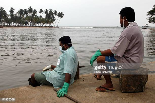Volunteers take a rest from cleaning dirt and debri as they look over a peaceful ocean January 9 2005 in Matara Sri Lanka Hundreds of locals living...