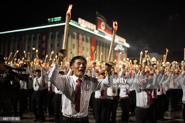 Volunteers take part in a torchlighting performance at Kim IlSung square in Pyongyang on October 10 2015 North Korea was marking the 70th anniversary...