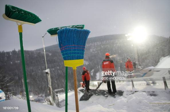 Volunteers tasked with clearing the jump of powder snow between the runners watch an athlete during the training run at the FIS Ski Jumping World Cup...