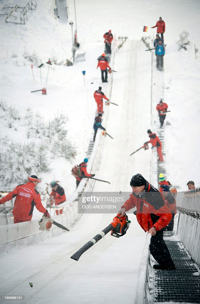 Volunteers try to clear the jump of powder snow between the runners during the training run at the FIS Ski Jumping World Cup on the Muehlenkopfschanze hill in Willingen, western Germany on February 8, 2013. Heavy snowfall made the conditions challenging for the athletes.