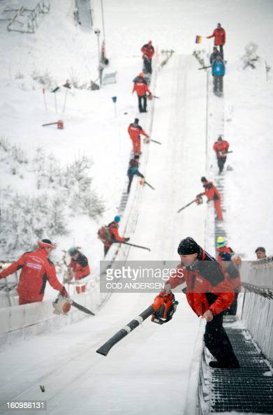 Volunteers try to clear the jump of powder snow between the runners during the training run at the FIS Ski Jumping World Cup on the...