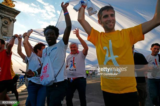 Volunteers unfold a giant banner with the logo of the Paris bid for the 2024 OLympic Games on the Alexandre III bridge in Paris on June 24 2017 in a...