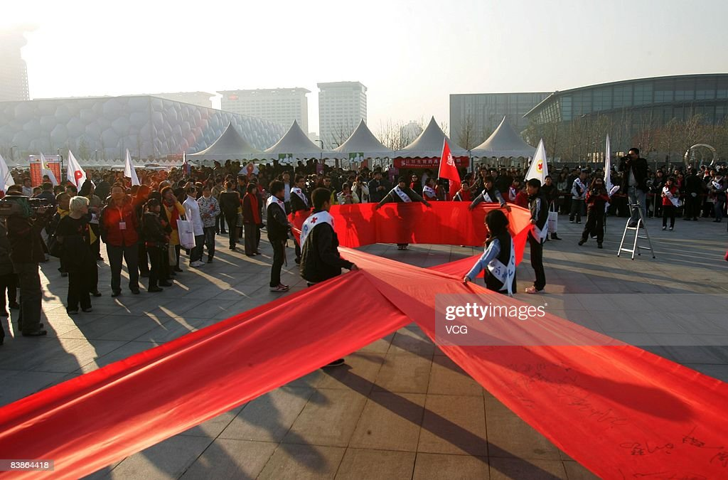 Volunteers unfold a red ribbon and let visitors sign their name on it during a World AIDS Day event in Beijing November 30, 2008 in Beijing, China. The World AIDS Day falls on December 1. This years theme is 'Stop AIDS. Keep the Promise'