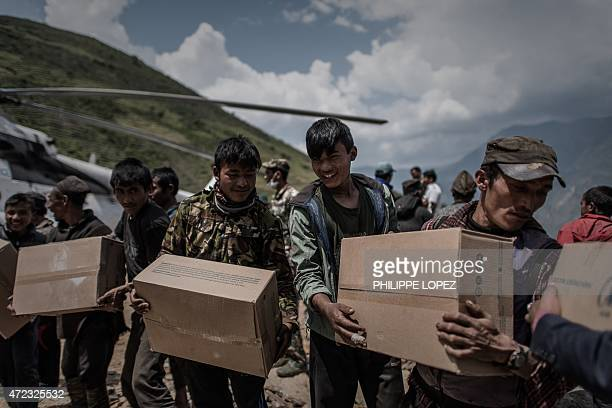 Volunteers unload relief supplies from a World Food Programme helicopter in the remote Kerauja village of Nepal's Gorkha district on May 6 2015 The...