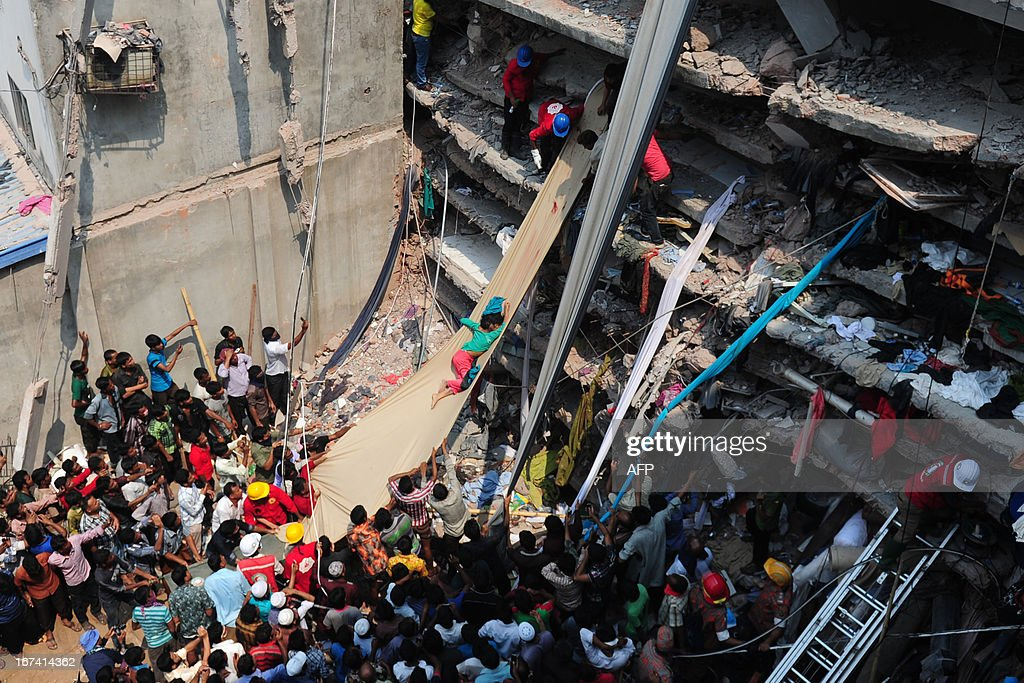 Volunteers use a length of textile as a slide to move dead victims recovered from the rubble after an eight-storey building collapsed in Savar, on the outskirts of Dhaka, on April 25, 2013. Survivors cried out to rescuers Thursday from the rubble of a block of garment factories in Bangladesh that collapsed killing 175 people, sparking criticism of their Western clients. AFP PHOTO/Munir uz ZAMAN