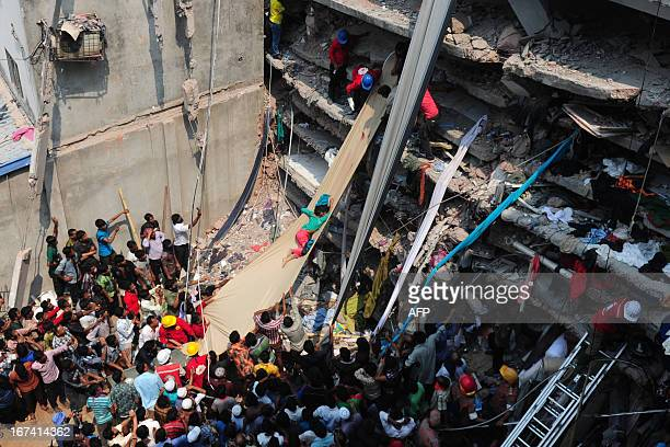 Volunteers use a length of textile as a slide to move dead victims recovered from the rubble after an eightstorey building collapsed in Savar on the...