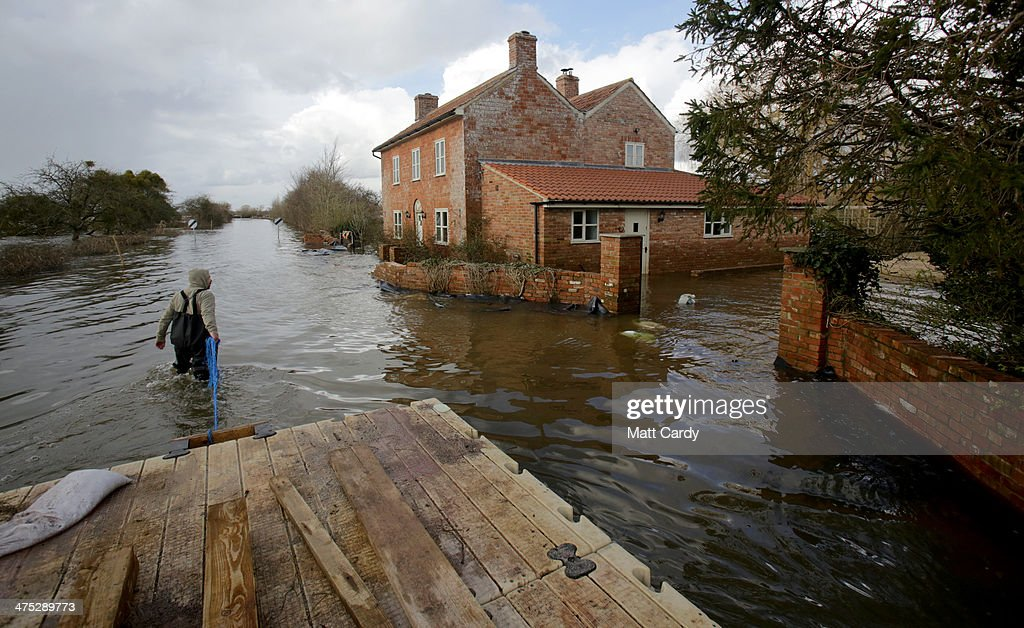 Volunteers use a pontoon to collect a car that has been cut off by flood waters at Burrowbridge on the Somerset Levels on February 27, 2014 in Somerset, England. According to the Met Office, England and Wales have experienced their wettest winter since records began in 1766, with parts of flood-hit southern England having experienced 83% more rain than average.