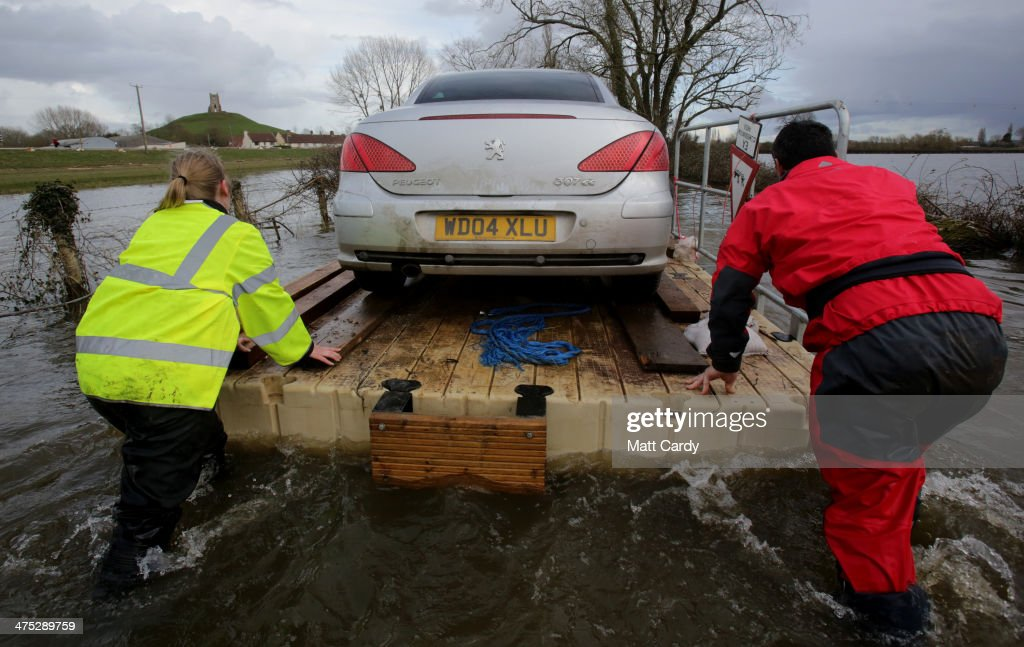 Volunteers use a pontoon to move a car that has been cut off by flood waters at Burrowbridge on the Somerset Levels on February 27, 2014 in Somerset, England. According to the Met Office, England and Wales have experienced their wettest winter since records began in 1766, with parts of flood-hit southern England having experienced 83% more rain than average.