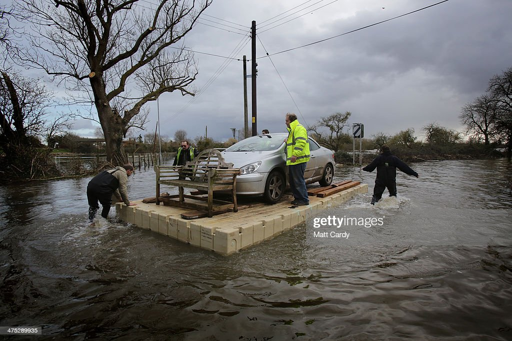Volunteers use a pontoon to move a car that has been cut off by flood waters at Burrowbridge on the Somerset Levels on February 27 2014 in Somerset...