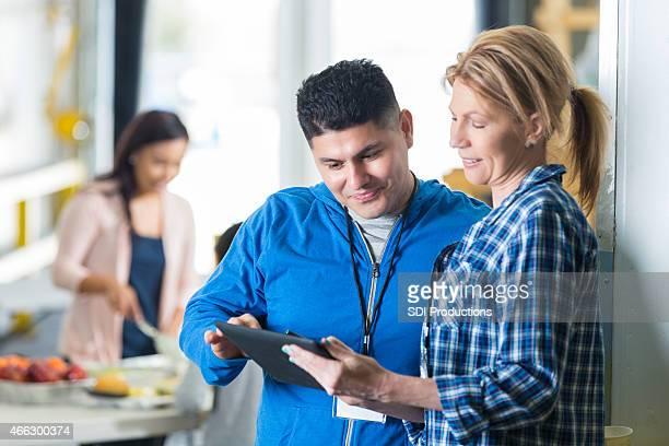 Volunteers using digital tablet in charity food bank