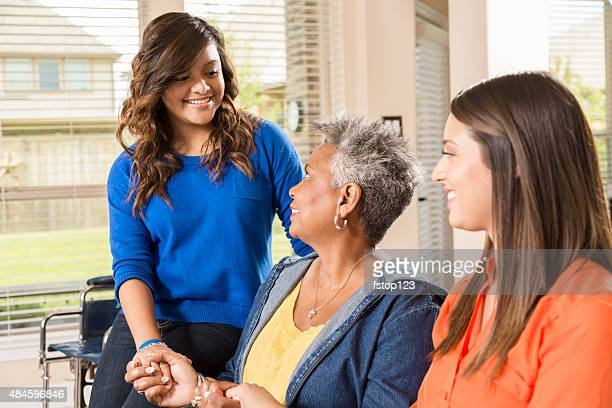 Volunteers visit with senior woman, grandmother in her home.