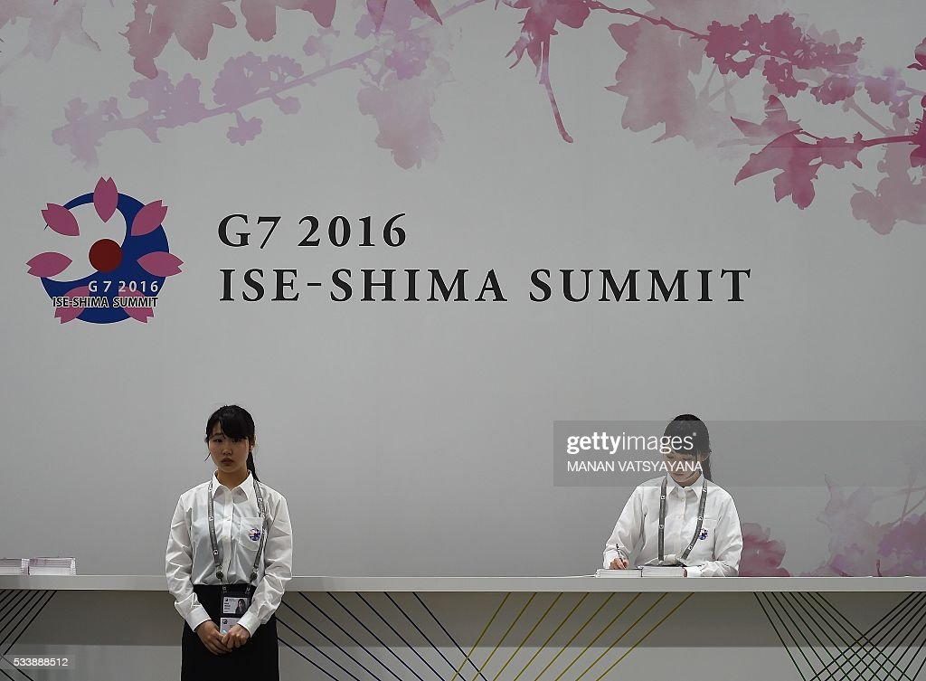 Volunteers wait for mediapersons at the reception desk of the 2016 Ise-Shima G7 Summit International Media Center in Ise-Shima, 300 kilometres southwest of Tokyo on May 24, 2016. The lacklustre global economy should take centre stage as world leaders gather in Japan this week, but with no agreement likely on igniting growth, Barack Obamas visit to the atomic-bombed city of Hiroshima looks set to capture the limelight. / AFP / MANAN