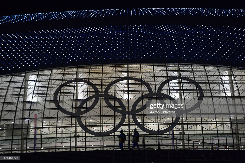Volunteers walk beneath the Olympic rings during closing ceremony for the Sochi 2014 Winter Olympics outside of the Bolshoy Ice Arena. Sochi 2014 Winter Olympics on Sunday, February 23, 2014 at Bolshoy Ice Arena.