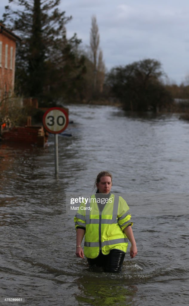 Volunteers walks behind a pontoon to collect a car that has been cut off by flood waters at Burrowbridge on the Somerset Levels on February 27, 2014 in Somerset, England. According to the Met Office, England and Wales have experienced their wettest winter since records began in 1766, with parts of flood-hit southern England having experienced 83% more rain than average.